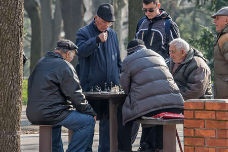 retirees: Belgrade, Serbia - February 27, 2016: The group retirees play chess in the park Editorial