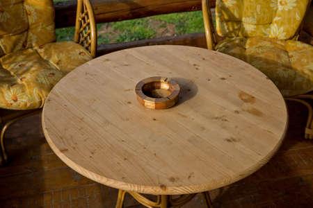 Portacenere in legno ad un tavolo rotondo in legno con sedie in bambù