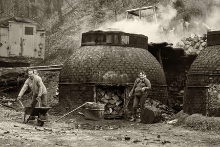 hemispherical: Klokocevac, Serbia - March 24, 2016: The production of charcoal in a traditional manner in the forest using beech wood