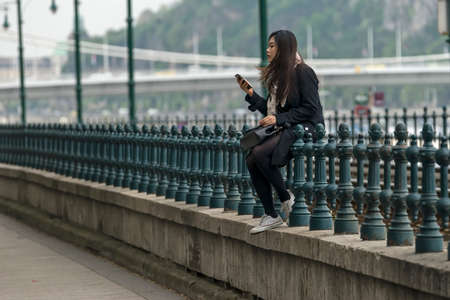 Budapest, Hungary - April 11,2016: A young Chinese girl sitting on the fence and play with mobile phone. Editorial
