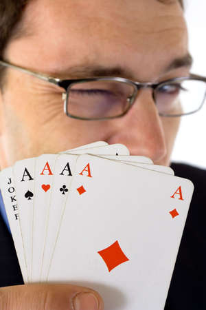 Winking man showing four aces and joker cards in foreground. Stock Photo - 2538867