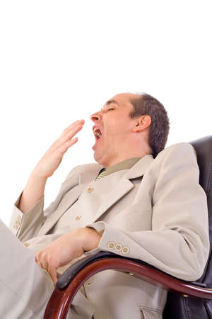 Yawning businessman siting in gray suit on black armchair