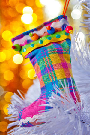 Decorative boots on a white Christmas tree. Colorful bokeh in the background. Stock Photo - 8262395
