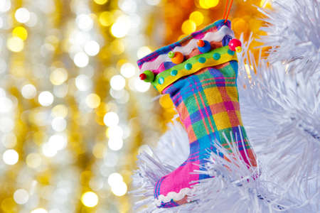 Decorative boots on a white Christmas tree. Colorful bokeh in the background. photo