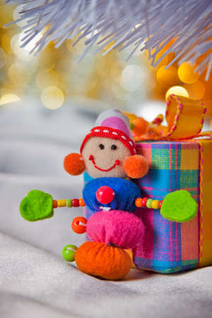 Decorative snowman with present box. Colorful bokeh in the background. photo