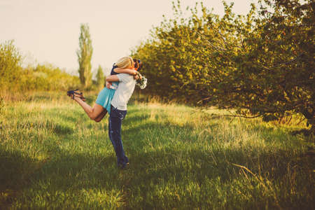 Loving couple hugging and kissing on a blossoming garden photo