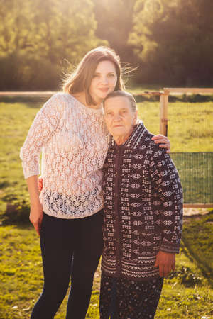 Young woman hugging a grandmother outdoors.
