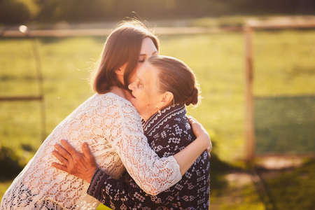 grandkids: Young woman hugging a grandmother outdoors.
