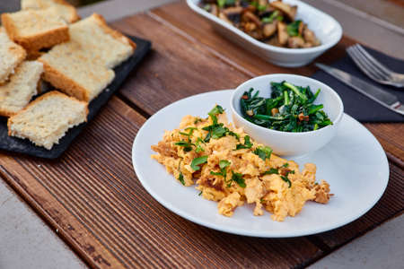 Snack from grated beans and greens, served with chopped mushrooms and seasoning, as well as slices of roasted homemade bread. Snack puree from legumes for spreading on toast Stock Photo