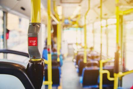 Botón rojo STOP en el bus. Autobús con pasamanos amarillos y asientos azules. Foto con el efecto del sol, resplandor en la lente de la luz. Interior espacioso del autobús, botón brillante con foco