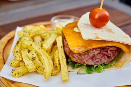 A huge juicy burger in a thin homemade pita bread with a sheet of green lettuce, melted cheddar cheese, veal cutlet and cherry tomato. Cheeseburger with French fries and white sauce on a wooden board