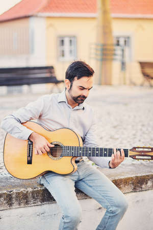 A cute stylish man with a beard sits on a concrete curb in the street and plays an acoustic guitar and smiles. The musician enjoys his music and creates a good mood for the people around him