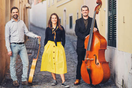 A musical group of three people on an old European street. The band consists of two men and one girl. Men with a double bass and a guitar. Unconventional creative people with musical instruments Stock Photo