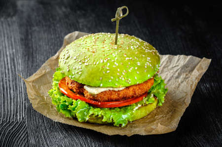 Green Burger fish cutlet and tomato. Black wood background