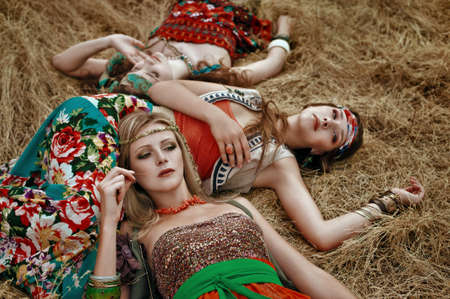 Beautiful hippie girls lies in dry grass