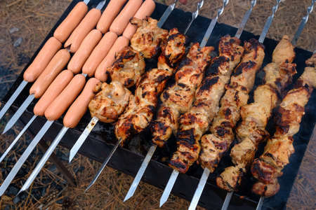 Preparation of shish kebab and sausages on outdoor charcoal grill 写真素材