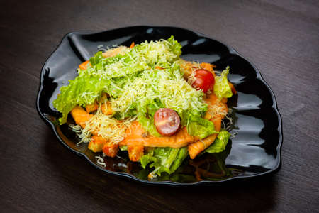 Caesar salad with chicken on a black plate on wooden table