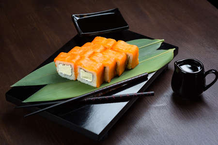 Rolls with salmon and cheese on the board with sauce and red chopsticks Stock Photo