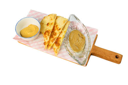 Focacha with sauce on a cutting board on white background, isolated
