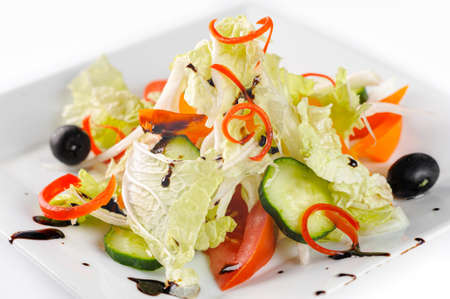 Vitamin salad with fresh vegetables on a white plate, closeup