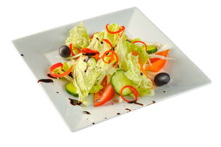Vitamin salad with fresh vegetables on a white plate on white background, closeup