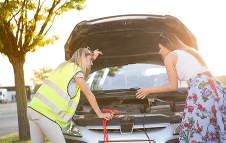 Two beautiful young women try to repair a broken car that has broken down on the road away from the city. Imagens