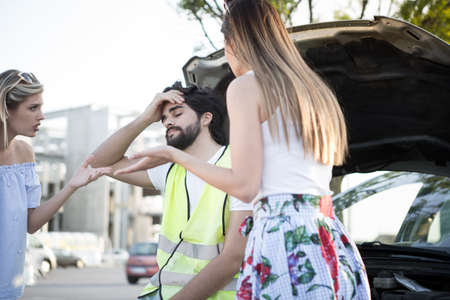 A handsome young man is worried because his car is corrupt and women are hysterical. Imagens