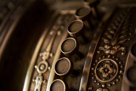 Der selektive Fokus auf die Knöpfe an den alten 19er-Kassen ist näher. Der Knopf ist viel getragen, aber die Nummern sind noch sichtbar.