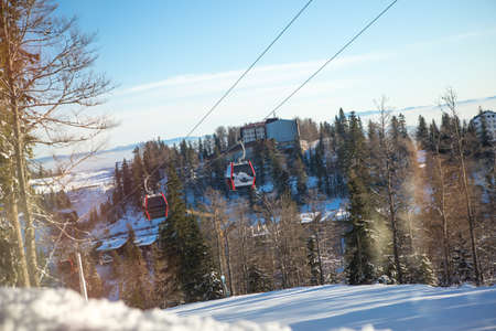 There is beautiful paved snow on the ski slope, and above the trail there is a ski lift with a gondola. Its a beautiful and sunny day. Stok Fotoğraf