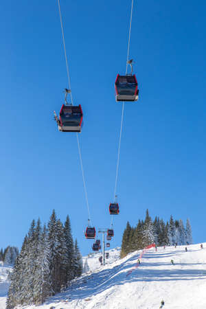 A brand new cable car is in use. The cable car is located above the ski slope. It's a beautiful sunny day on the mountain.