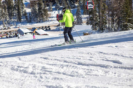 A beautiful sunny day on the mountain, one skier in a yellow jacket is on the course and slowly descends the slope.