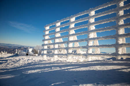 Windproof fence covered with snow on top of mountain in winter season. The day is sunny and the sky is clear and blue.