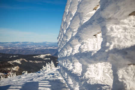 Windproof fence covered with snow on top of mountain in winter season. The day is sunny and the sky is clear and blue. Copy Space. Snow.