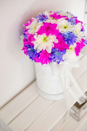 Close-up on a floral arrangement of chrysanthemum flowers. Chrysanthemums are white, purple and pink, they are in a hand-made white box. Behind is a white background.