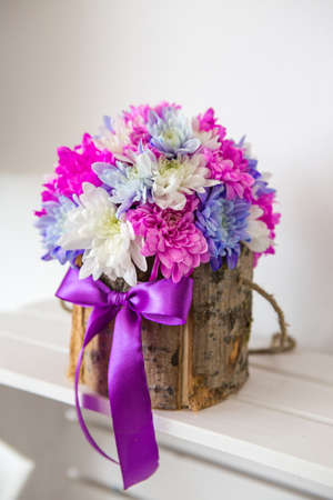 Close-up on a floral arrangement of chrysanthemum flowers. Chrysanthemums are white, purple and pink, they are contained in a handmade box made of bark of wood. Behind is a white background.