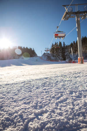 A beautiful sunny day on the mountain, the sun glows with a six-seat ski lift. Below the cable car there is a ski slope and skis and a pine forest around.