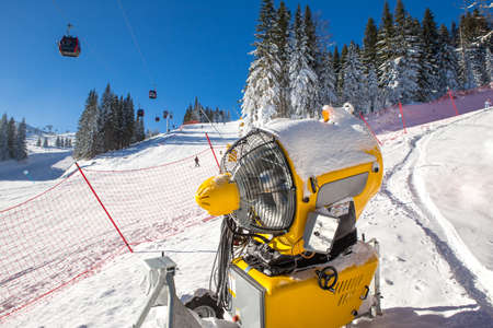The snow machine is located on the ski slope. It is a beautiful day on the mountain and there is enough snow so the machine is not turned on. Banque d'images - 140615569