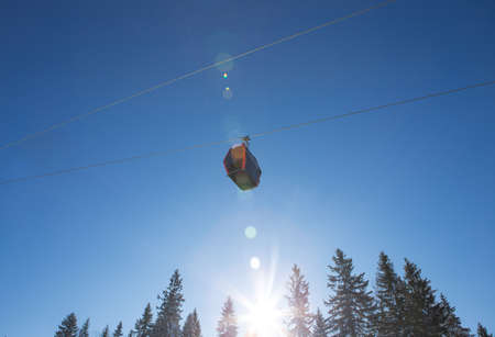 It's a beautiful sunny day on the mountain. There are two gondolas on the cable car and behind them is a beautiful blue sky. Banco de Imagens