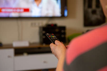A senior woman sits in front of the television watching television. She holds a remote control in her hand that she points at the TV because she wants to change the channel. The focus is on the remote control. 版權商用圖片