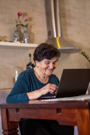 A senior woman with black short hair in a turquoise shirt is typing on a gray laptop keyboard. She laughs and is thoughtful as she looks at the monitor from her laptop computer. She is at the wooden dining table in the kitchen. Foto de archivo
