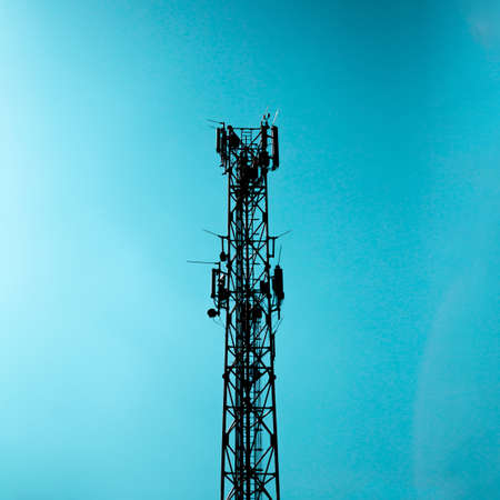 Radio signal tower for mobile telephony and internet. The tower is made of metal construction and behind it is a blue sky.