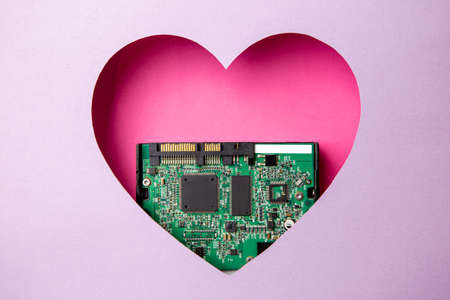 The green printed circuit board with microprocessors is located in a pink heart-shaped cavity. All around is purple. Copy Space. Love. Technology. Artificial intelligence. Robotics. Reklamní fotografie