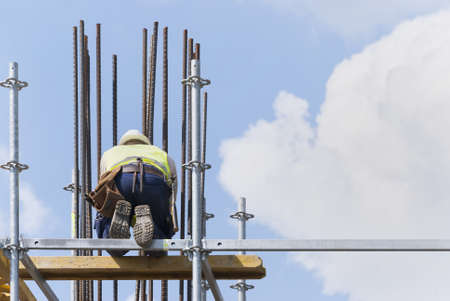 A construction worker on a high wall of a new building photo
