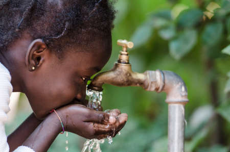 Clean Freshwater Scarcity Symbol: Black Girl Drinking from Tap. Young African girl drinking clean water from a tap. Hands with water pouring from a tap in the streets of the city Bamako, Mali. Stock Photo