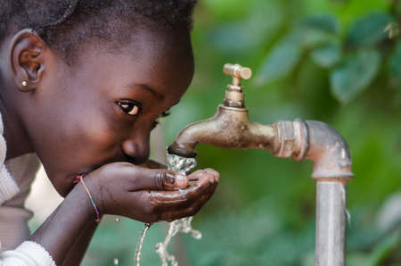 Schöne afrikanische Kind von einem Tap Trinken (Wasserknappheit Symbol). Junge Mädchen in Afrika sauberes Wasser aus einem Wasserhahn zu trinken. Wasser aus einem Wasserhahn in den Straßen der afrikanischen Stadt Bamako, Mali Gießen. Standard-Bild