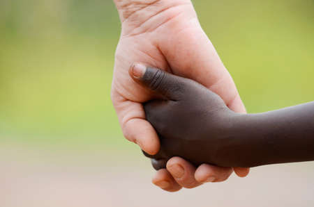 Hope symbol - African child and white Caucasian woman holding hands outdoors as a symbol for hope, peace and tranquility