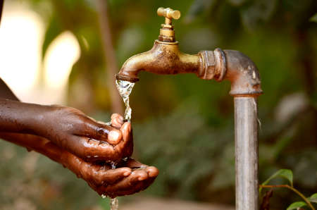 African child reaching for water under a tap as a symbol for water scarcity in African countries Banco de Imagens