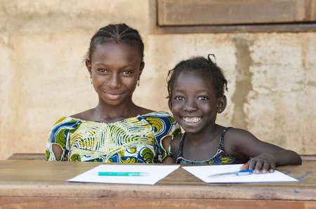 学校環境 (学校教育記号) で勉強して笑みを浮かべて二人のアフリカ民族子供 写真素材