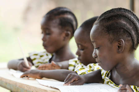 Two beautiful African girls and one African boy reading and writing at school as an educational symbol outside their school in Bamako, Mali. Beautiful education symbol background. Stock Photo