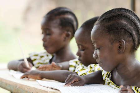 Zwei schöne afrikanische Mädchen und ein afrikanischer Junge, die in der Schule als pädagogisches Symbol außerhalb ihrer Schule in Bamako, Mali lesen und schreiben. Schöner Bildungssymbolhintergrund. Standard-Bild
